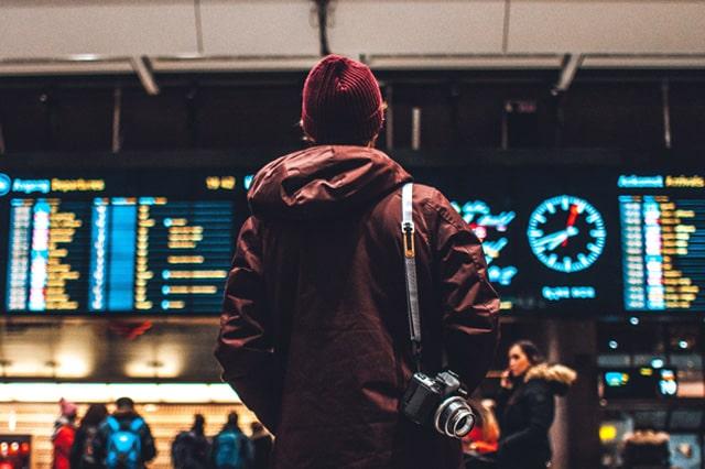 駅の時刻表を見ている男性
