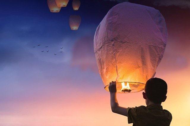 空に風船を飛ばす少年