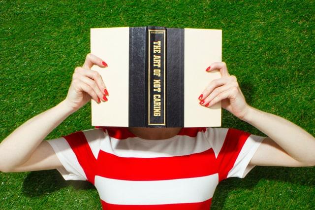 本を顔の前に持つ人