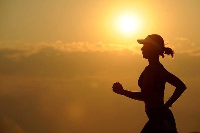 夕暮れに走る女性