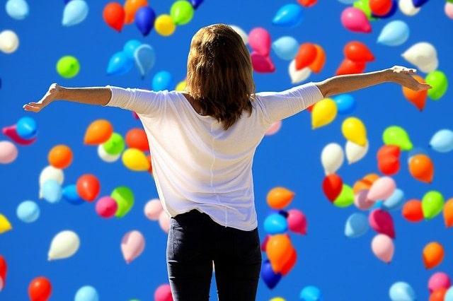 風船と手を広げる女性
